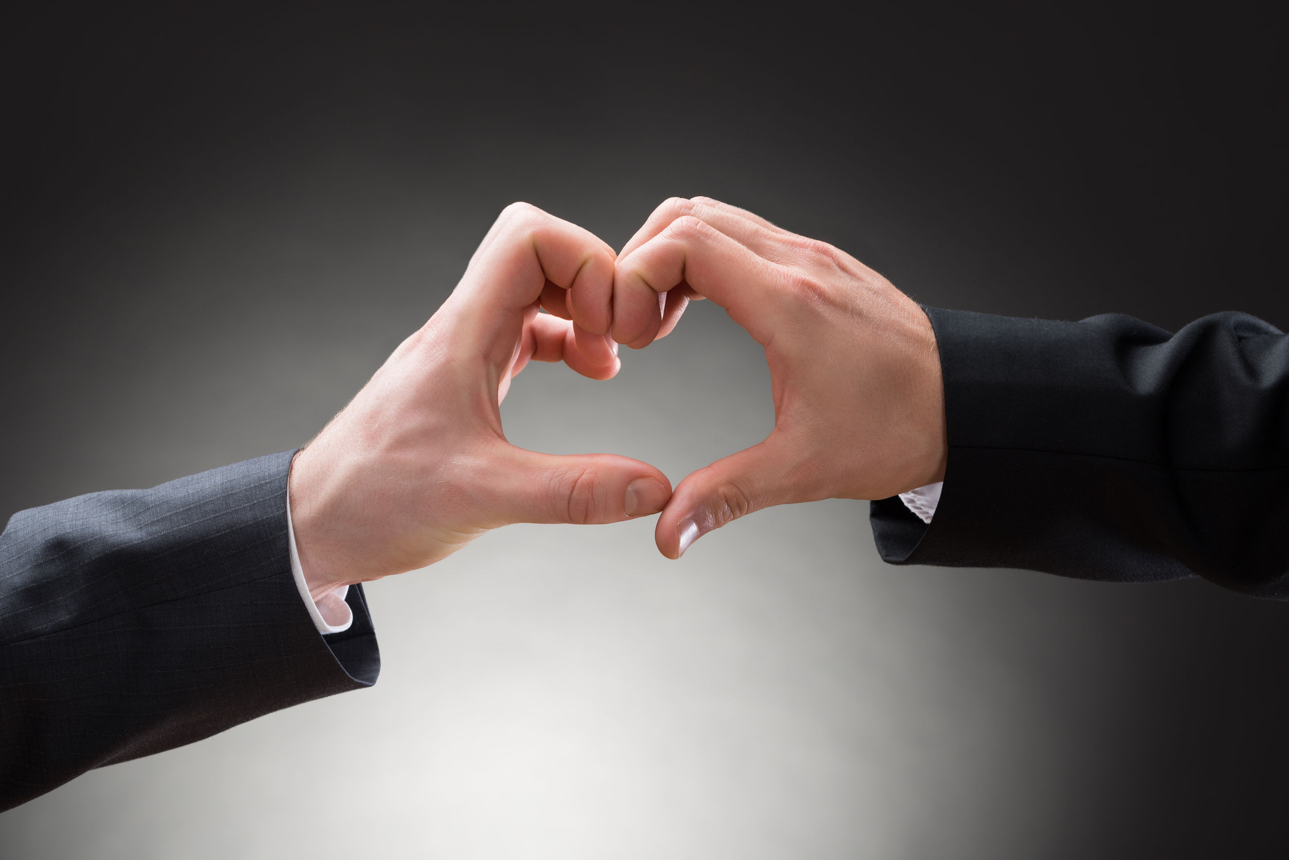 close-up of two gay men making heartshape with hands