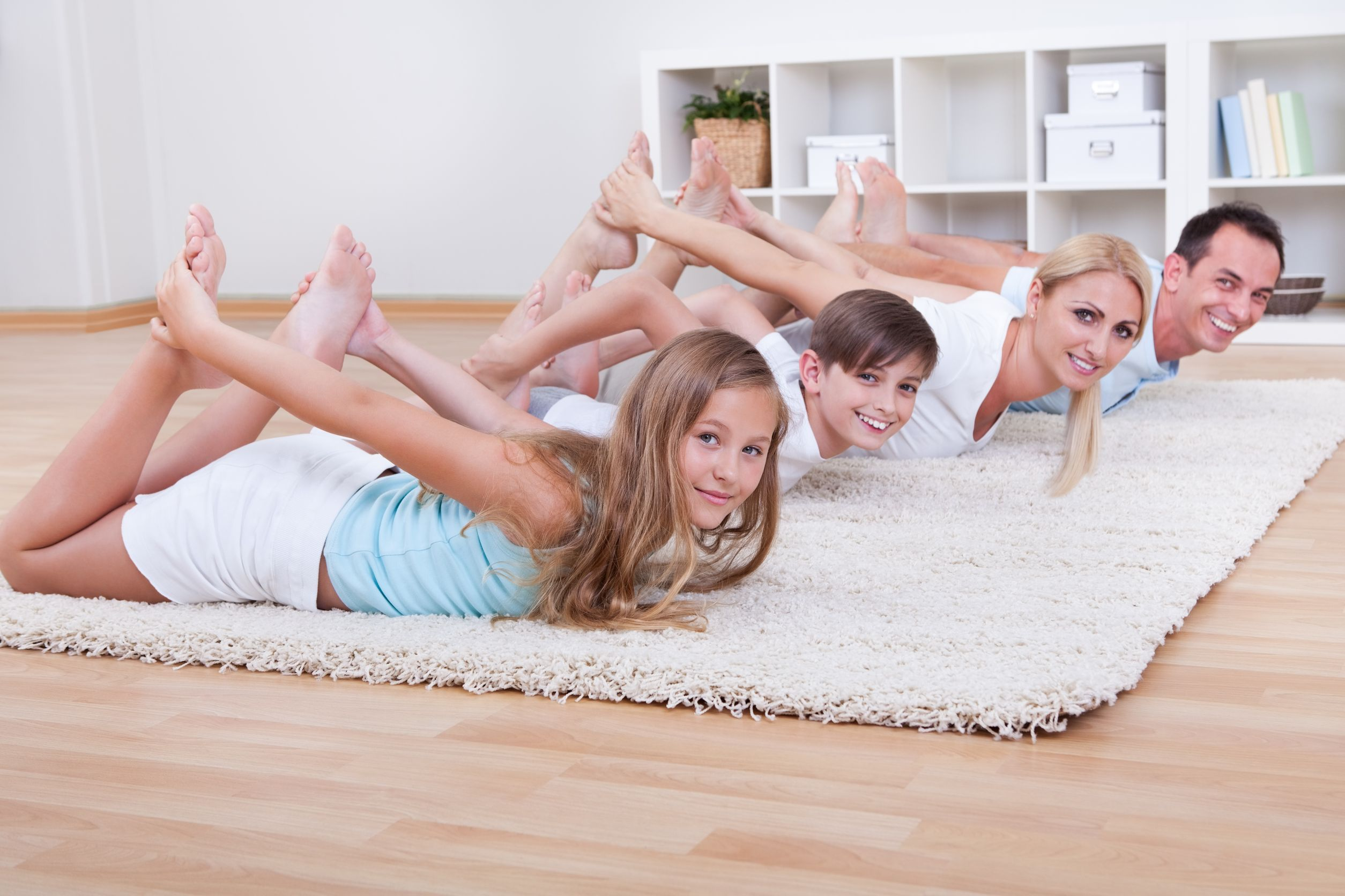 family doing stretching exercises laying on the carpet at home