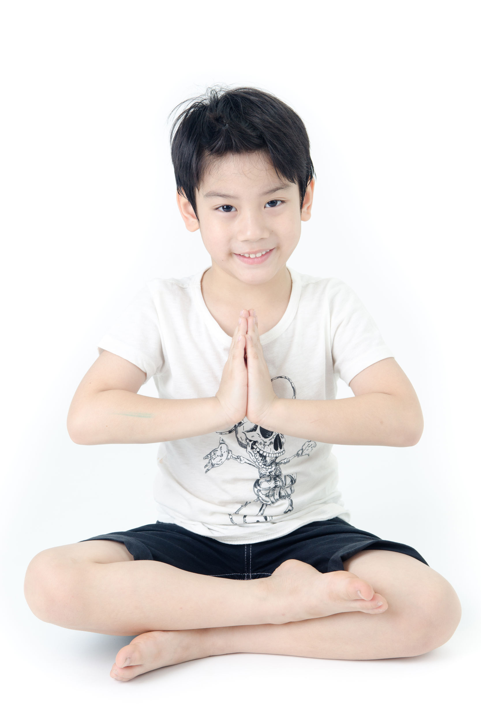 portrait of asian cute boy practicing yoga on white background .